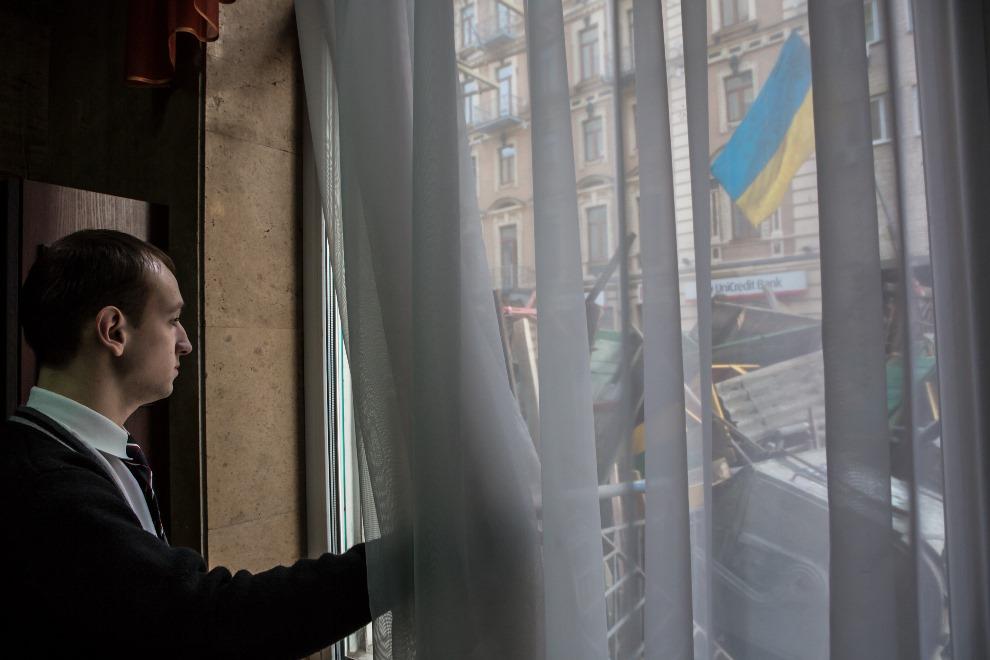 34.UKRAINA, Kijów, 19 lutego 2014: Pracownik hotelu przygląda się zamieszkom na ulicy. (Foto: Brendan Hoffman/Getty Images)