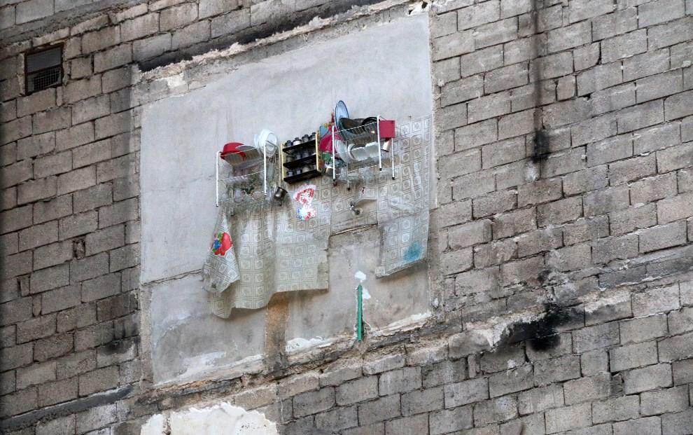 3.SYRIA, Aleppo, 9 lutego 2014: Suszarka z naczyniami na ścianie ostrzelanego budynku. AFP PHOTO/AMC/ZEIN AL-RIFAI