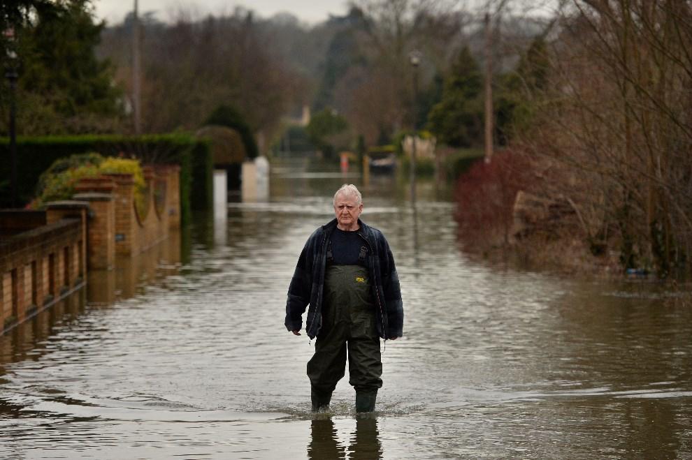 4.WIELKA BRYTANIA, Wraysbury, 10 lutego 2014: Mieszkaniec Wraysbury na zalanej wodą ulicy. AFP PHOTO / BEN STANSALL