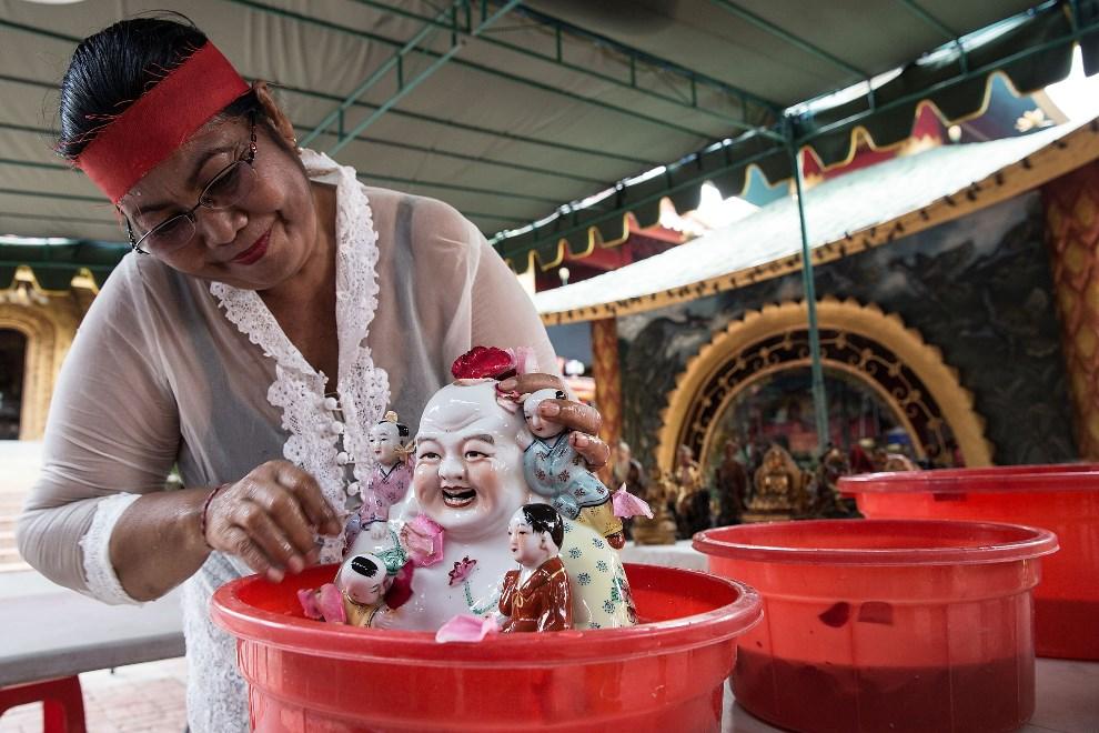 4.INDONEZJA, Denpasar, 25 stycznia 2014: Kobieta czyszcząca posążki w świątyni Dwipayana Tanah Kilap. (Foto:  Agung Parameswara/Getty Images)