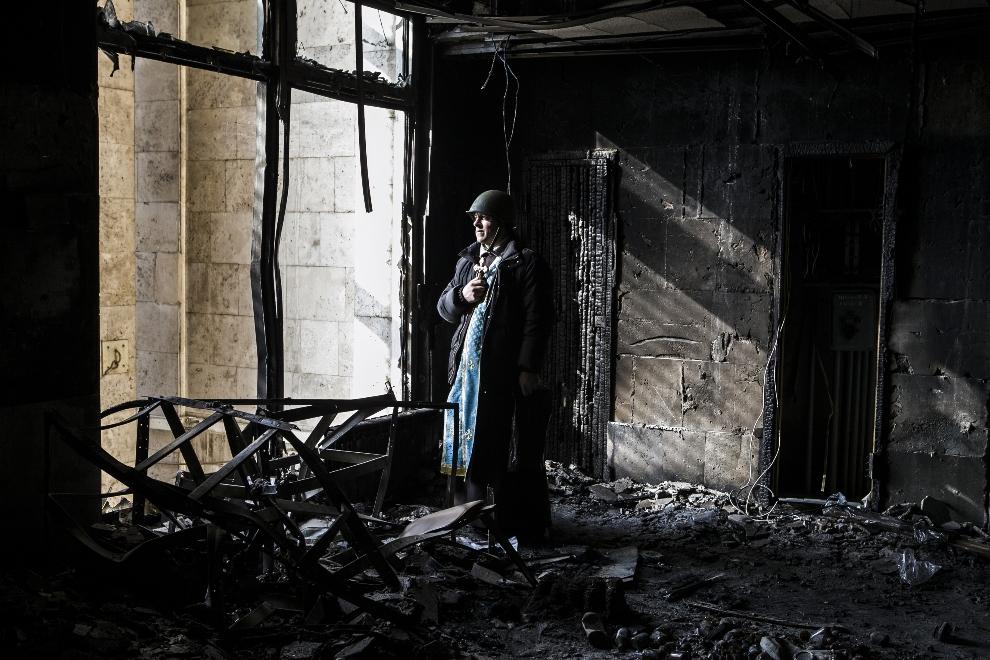 5.UKRAINA, Kijów, 21 lutego 2014: Kapłan w spalonym wnętrzu budynku związków zawodowych. AFP PHOTO / SANDRO MADDALENA