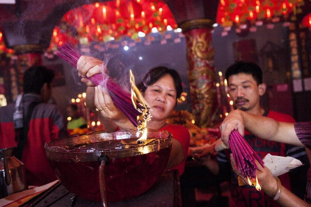 5.INDONEZJA, Tangerang, 31 stycznia 2014: Kobieta zapalające kadzidła w świątyni Bun San Bio. (Foto:  Oscar Siagian/Getty Images)