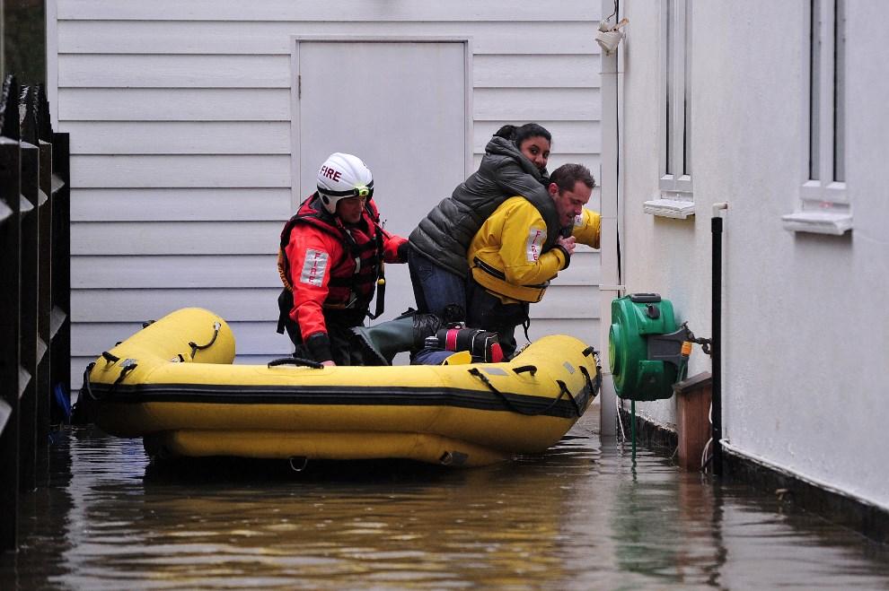 6.WIELKA BRYTANIA, Wraysbury, 11 lutego 2014: Strażacy pomagają przy ewakuacji mieszkańców. AFP PHOTO / CARL COURT