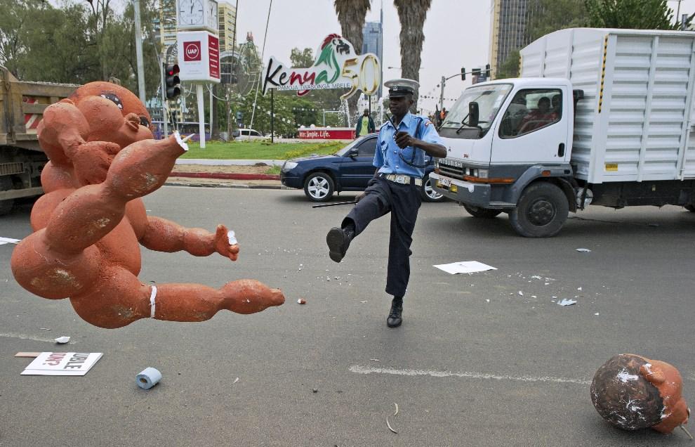 6.KENIA, Nairobi, 13 lutego 2014: Policjant kopie styropianową figurkę zostawioną na ulicy przez protestujących.. AFP PHOTO / CARL DE SOUZA