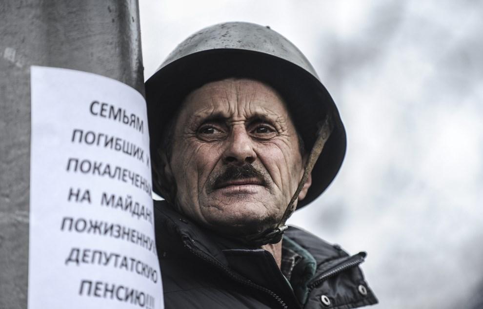 6.UKRAINA, Kijów, 22 lutego 2014: Mężczyzna przed budynkiem parlamentu. AFP PHOTO/ BULENT KILIC
