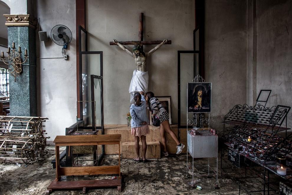 6.FILIPINY, Leyte, 17 listopada 2013: Kobiety modlące się w zniszczonym kościele. (Foto: Chris McGrath/Getty Images)