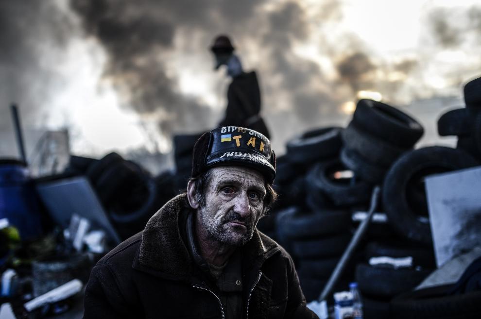 7.UKRAINA, Kijów, 21 lutego 2014: Mężczyzna na barykadzie w centrum miasta. AFP PHOTO/BULENT KILIC