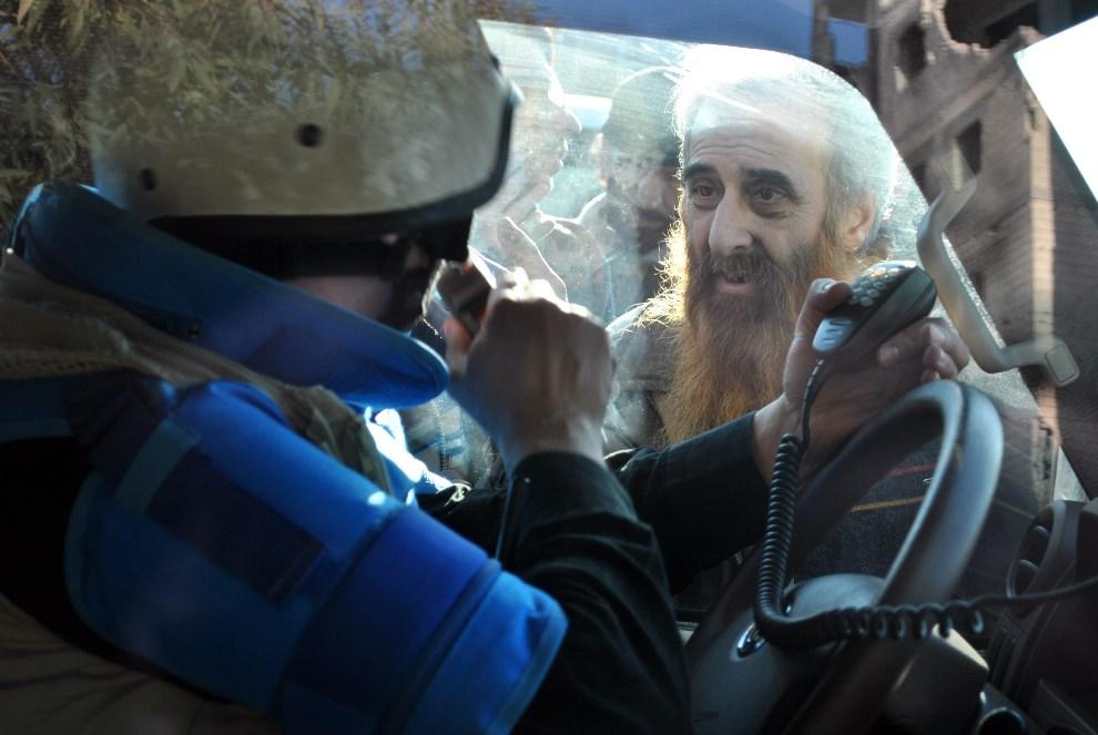 8.SYRIA, Homs, 9 lutego 2014: Pracownik misji ONZ stara się przejechać przez oblegający go tłum. AFP PHOTO / BASSEL TAWIL