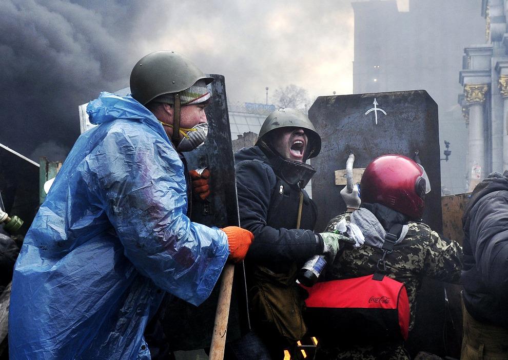 8.UKRAINA, Kijów, 20 lutego 2014: Protestujący starają się zająć nowe pozycje podczas walk w centrum miasta. AFP PHOTO / LOUISA GOULIAMAKI