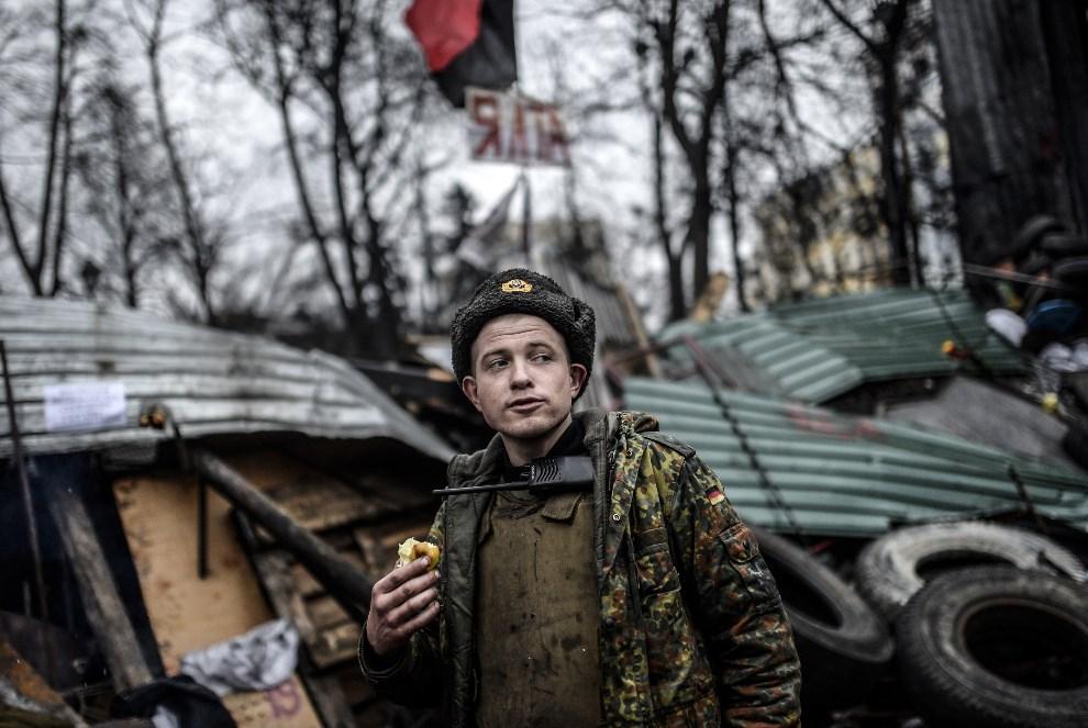 8.UKRAINA, Kijów, 25 lutego 2014: Mężczyzna jedzący jabłko na Placu Niepodległości. AFP PHOTO / BULENT KILIC