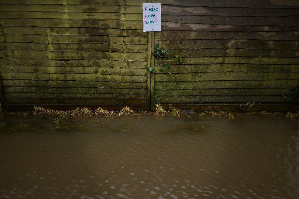 """9.WIELKA BRYTANIA, Thorney, 26 stycznia 2014: Kartka z napisem """"Proszę jechać powoli"""" przymocowana do ogrodzenia jednego z domów. AFP PHOTO/BEN STANSALL"""
