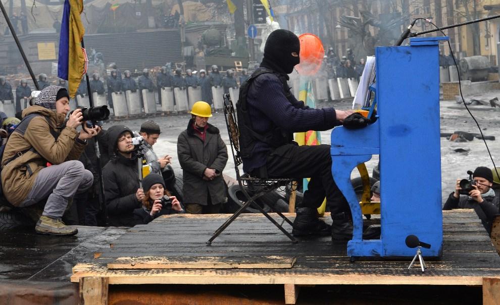 9.UKRAINA, Kijów, 10 lutego 2014: Antyrządowy aktywista gra na pianinie w trakcie trwających protestów. AFP PHOTO/ SERGEI SUPINSKY