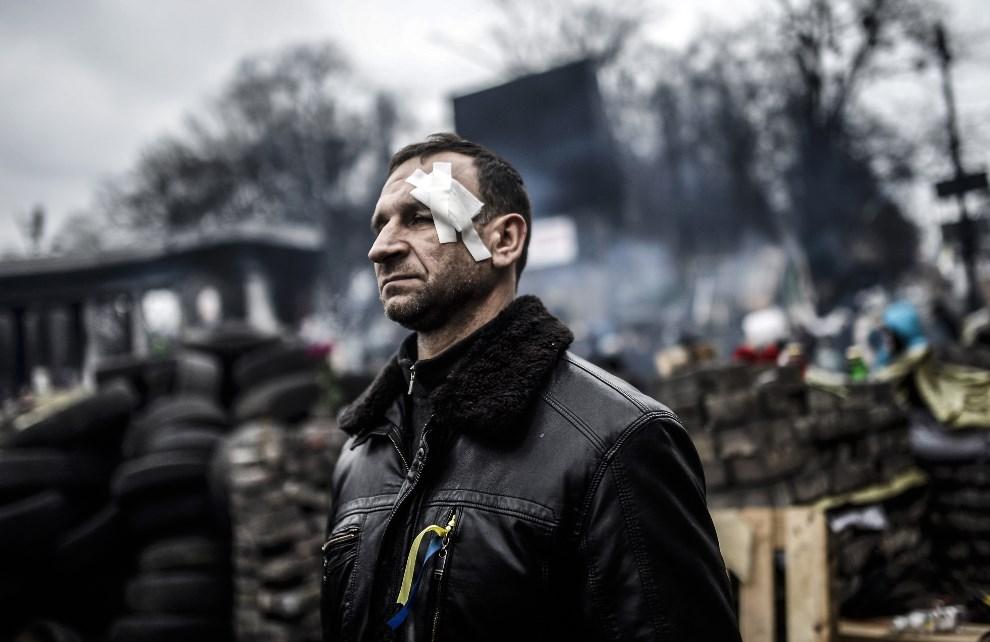9.UKRAINA, Kijów, 25 lutego 2014: Mężczyzna ranny w trakcie walk w Kijowie. AFP PHOTO / BULENT KILIC