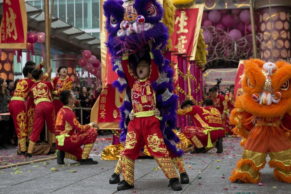 """9.CHINY, Hongkong, 4 lutego 2014: Uczestnicy parady noworocznej wykonują """"taniec lwa"""". AFP PHOTO / ALEX OGLE"""