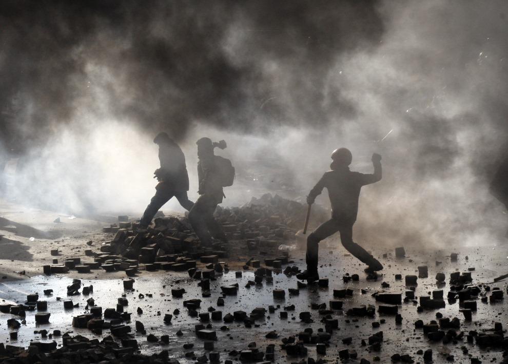 9.UKRAINA, Kijów, 18 lutego 2014: Protestujący mężczyźni obrzucają kamieniami oddziały milicji. AFP PHOTO/ ANATOLII STEPANOV