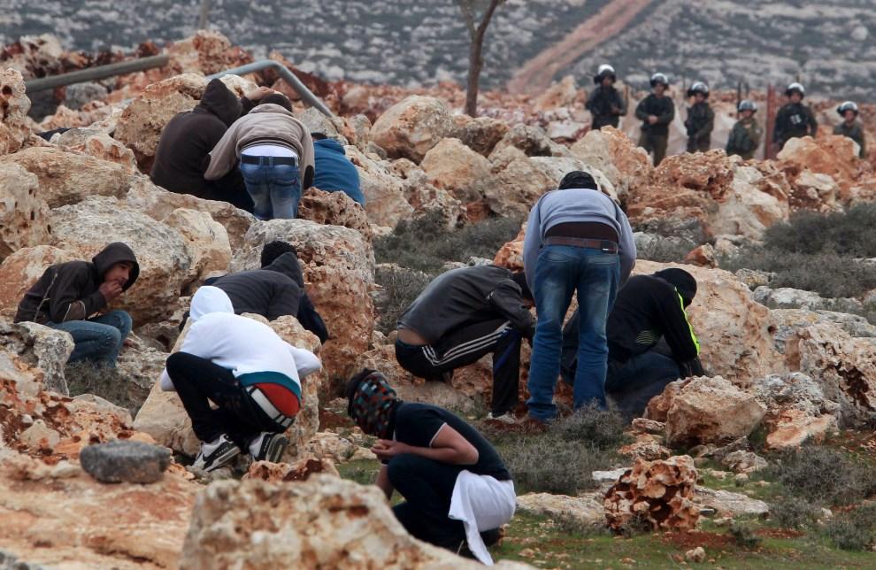 9. ZACHODNI BRZEG, Qusra, 6 lutego 2014: Palestyńczycy chowają się za głazami podczas starcia z żołnierzami izraelskimi. AFP PHOTO/JAAFAR ASHTIYEH