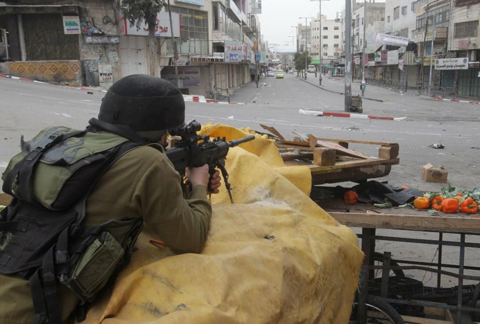 10.ZACHODNI BRZEG, Hebron, 17 marca 2014: Izraelski żołnierz w trakcie starć z Palestyńczykami. AFP PHOTO/HAZEM BADER
