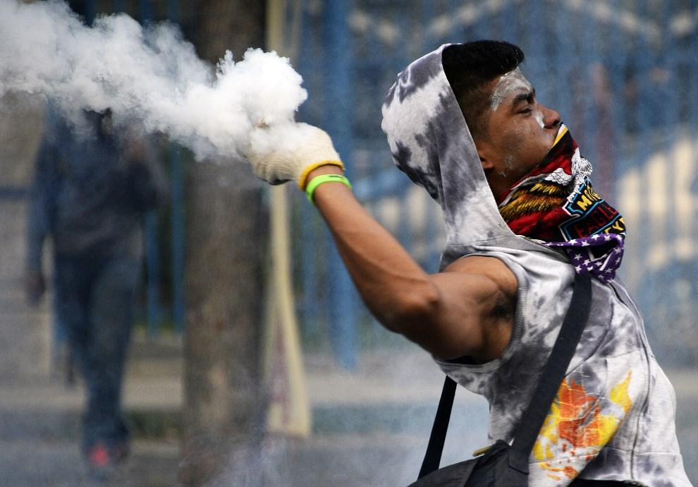 11.WENEZUELA, Caracas, 2 marca 2014: Protestujący odrzuca pojemnik z gazem łzawiącym w kierunku policjantów. AFP PHOTO / JUAN BARRETO