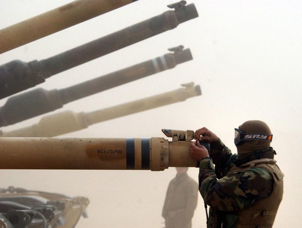 12.KUWEJT, 3 lutego 2003: Zasłanianie wlotu armaty podczas burzy piaskowej. (Foto: Scott Nelson/Getty Images)