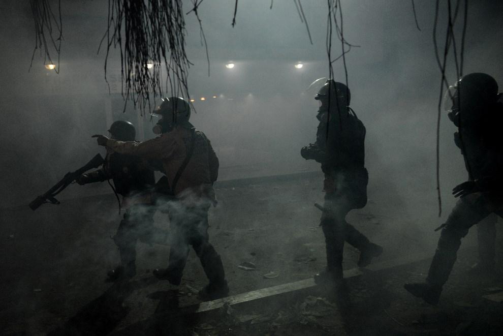 13.WENEZUELA, Caracas, 3 marca 2014: Gwardziści ostrzeliwują protestujących pojemnikami z gazem łzawiącym. AFP PHOTO /LEO RAMIREZ