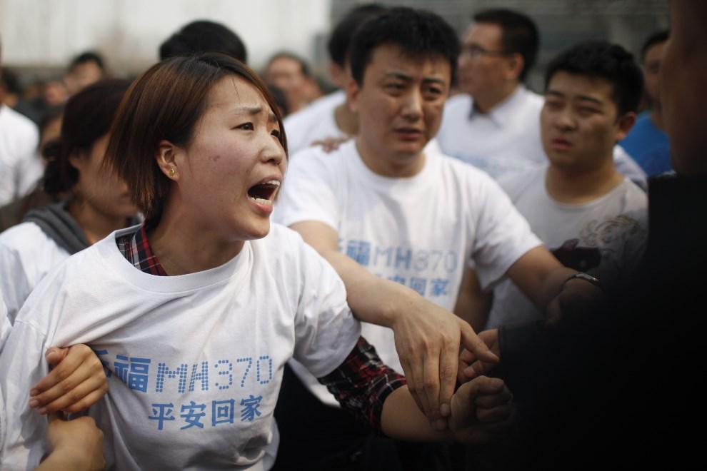 13.CHINY, Pekin, 25 marca 2014: Uczestniczka protestów przed ambasadą Malezji w Pekinie. AFP PHOTO CHINA OUT