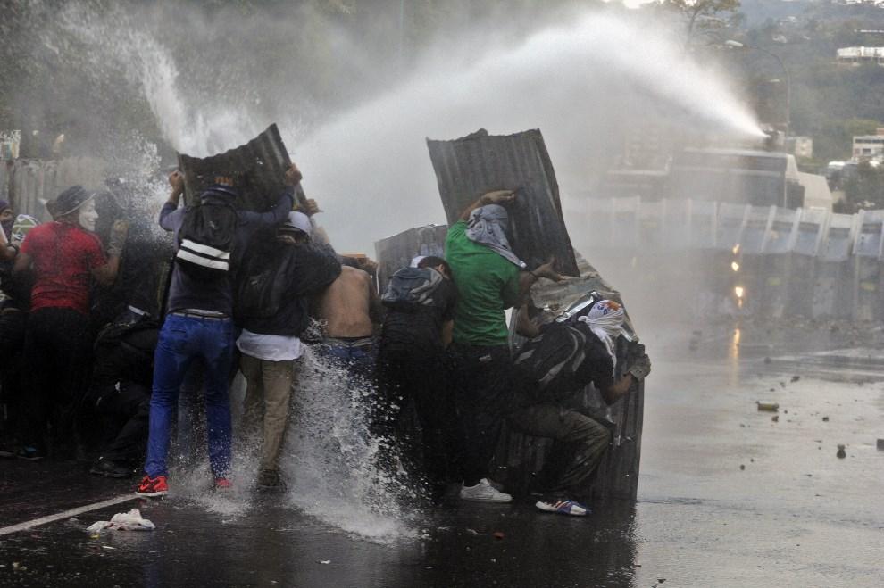 14.WENEZUELA, Caracas, 28 lutego 2014: Demonstranci zasłaniają się przed wodą z armatki wodnej. AFP PHOTO/ LEO RAMIREZ