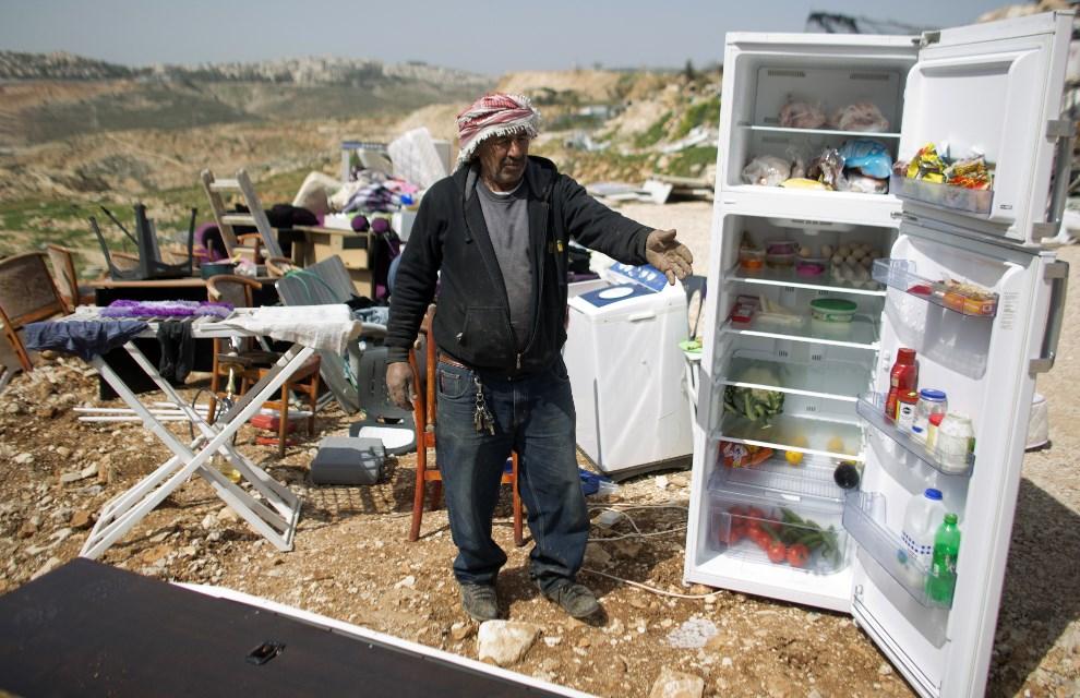 14.IZRAEL, Jerozolima, 19 marca 2014: Palestyńczycy zbierają swój dobytek z domu zniszczonego przez Izraelskie buldożery. AFP PHOTO/AHMAD GHARABLI