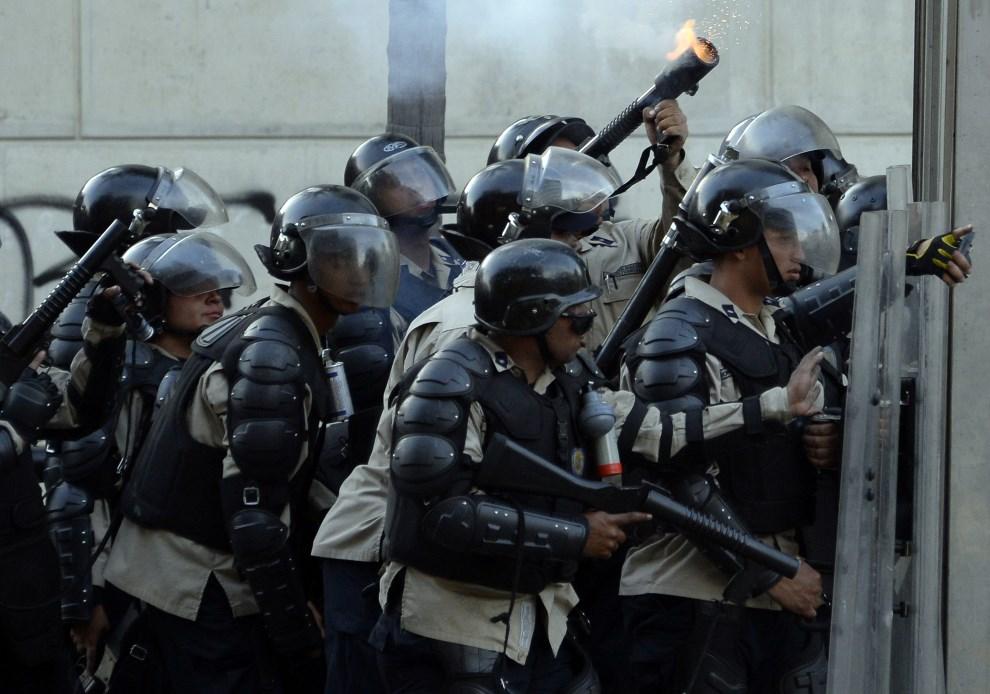 15.WENEZUELA, Caracas, 22 lutego 2014: Policjanci przygotowujący się do ataku na pozycje opozycjonistów. AFP PHOTO/ JUAN BARRETO