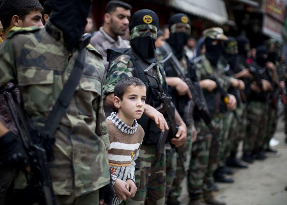 15.STREFA GAZY, Khan Yunis, 11 marca 2014: Palestyńskie chłopiec między członkami Brygady Al-Quds. AFP PHOTO / MAHMUD HAMS