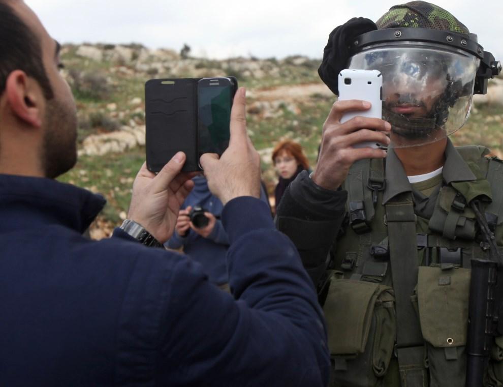 15.ZACHODNI BRZEG, Nabi Saleh, 14 marca 2014: Palestyńczyk i izraelski żołnierz robią sobie zdjęcia podczas zamieszek. AFP PHOTO / ABBAS MOMANI