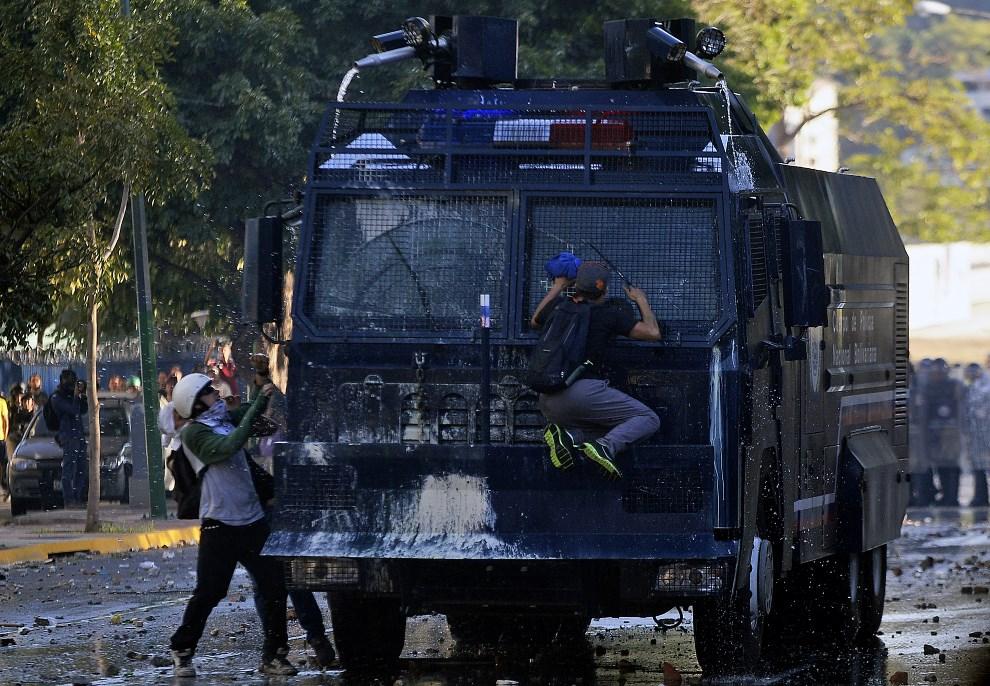 16.WENEZUELA, Caracas, 25 lutego 2014: Protestujący atakują armatkę wodną. AFP PHOTO/ JUAN BARRETO