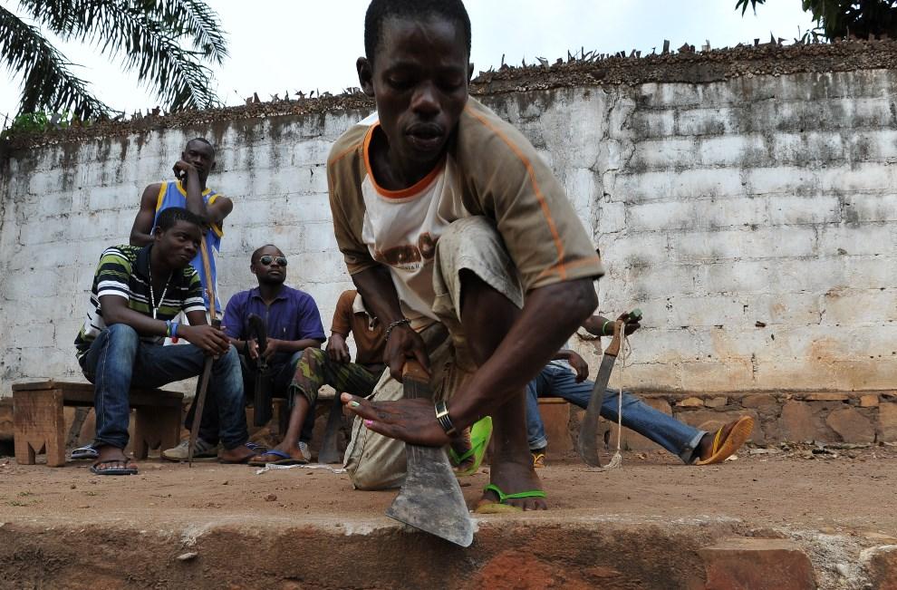 16.REPUBLIKA ŚRODKOWOAFRYKAŃSKA, Bangui, 12 marca 2014: Mężczyzna ostrzy maczetę przed wyjściem na patrol. AFP-PHOTO/ SIA KAMBOU