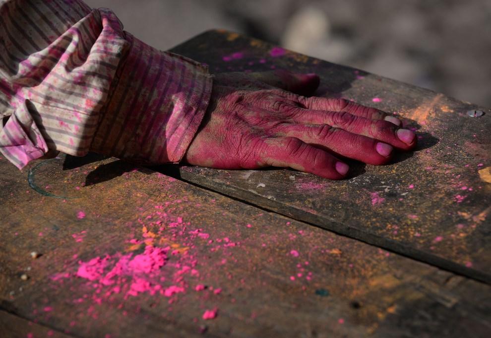 16.INDIE, New Delhi, 17 marca 2014: Dłoń mężczyzna pokryta kolorową farbą. AFP PHOTO /SAJJAD HUSSAIN
