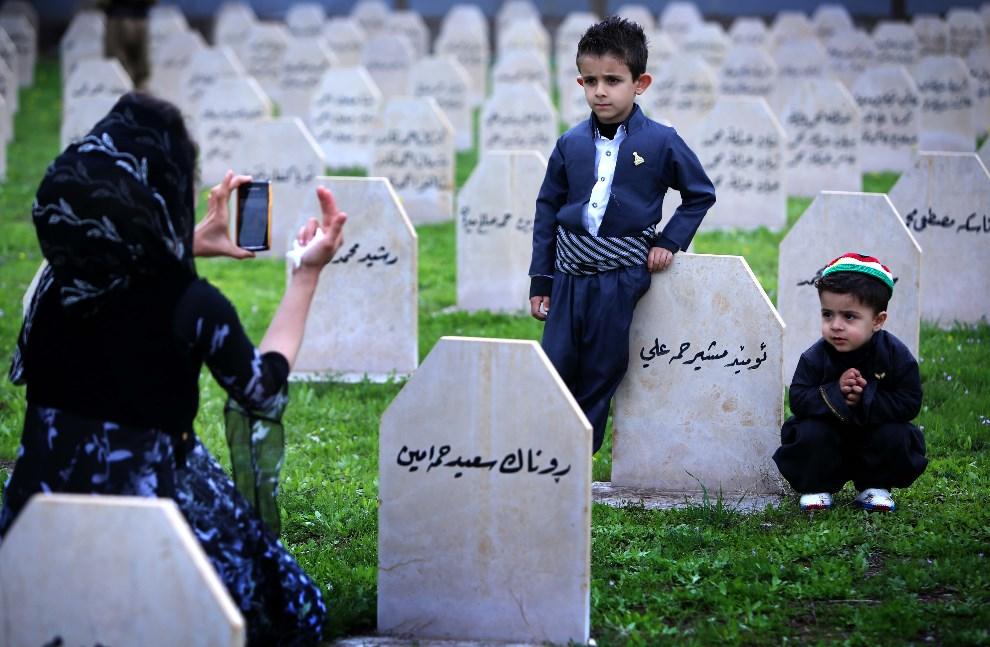 16.IRAK, Halabja, 16 marca 2014: Kurdyjska rodzina odwiedza grób bliskiej osoby, zabitej w trakcie ataku chemicznego wojsk Saddama Husajna. AFP PHOTO/SAFIN HAMED