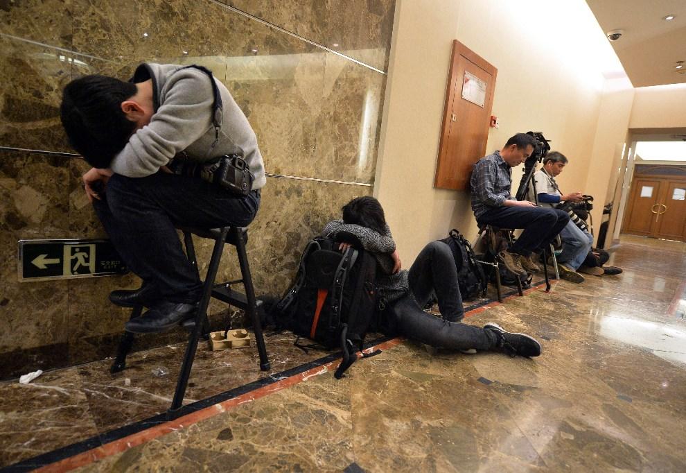 16.CHINY, Pekin, 23 marca 2014: Dziennikarze w oczekiwaniu na przybycie bliskich pasażerów zaginionego samolotu. AFP PHOTO / Mark RALSTON