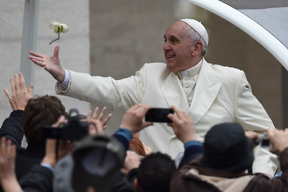 16.WATYKAN, 26 marca 2014: Papież Franciszek stara się złapać rzuconą jego kierunku różę. AFP PHOTO / VINCENZO PINTO