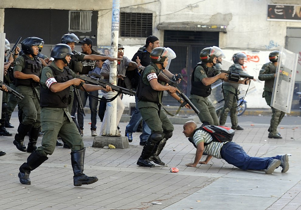 17.WENEZUELA, Caracas, 12 lutego 2014: Gwardziści zatrzymują jednego z protestujących. AFP PHOTO / LEO RAMIREZ