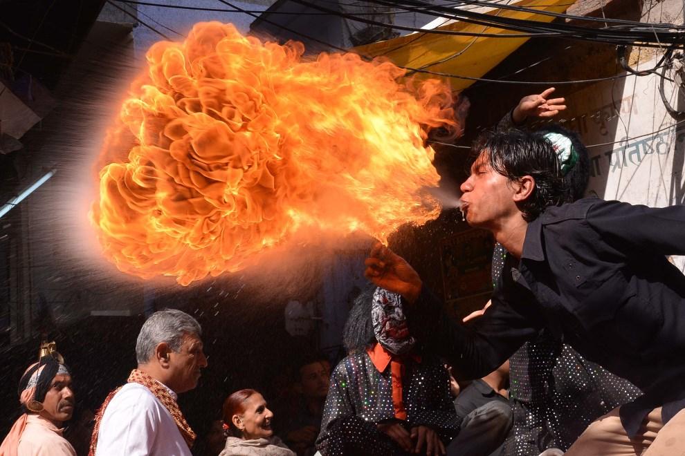 17.INDIE, Amritsar, 12 marca 2014: Mężczyzna zabawiający ludzi przybywających na obchody Holi. AFP PHOTO/NARINDER NANU