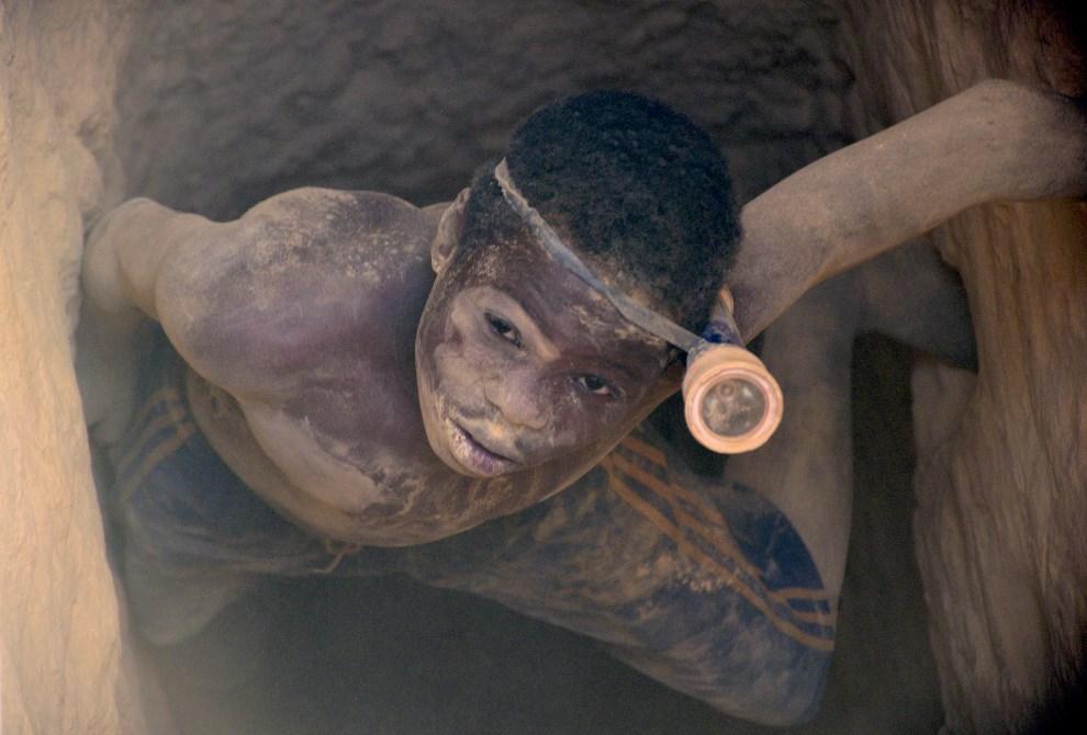 17.BURKINA FASO, Mogtedo, 20 lutego 2014: Chłopak pracujący w nielegalnej kopalni złota, wychodzi z szybu. AFP PHOTO / AHMED OUOBA