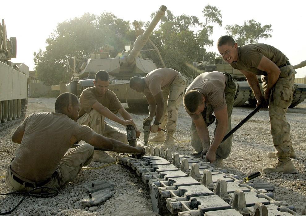 18.IRAK, Bagdad, 28 sierpnia 2004: Żołnierze naprawiają uszkodzą gąsienicę. AFP PHOTO/LIU Jin