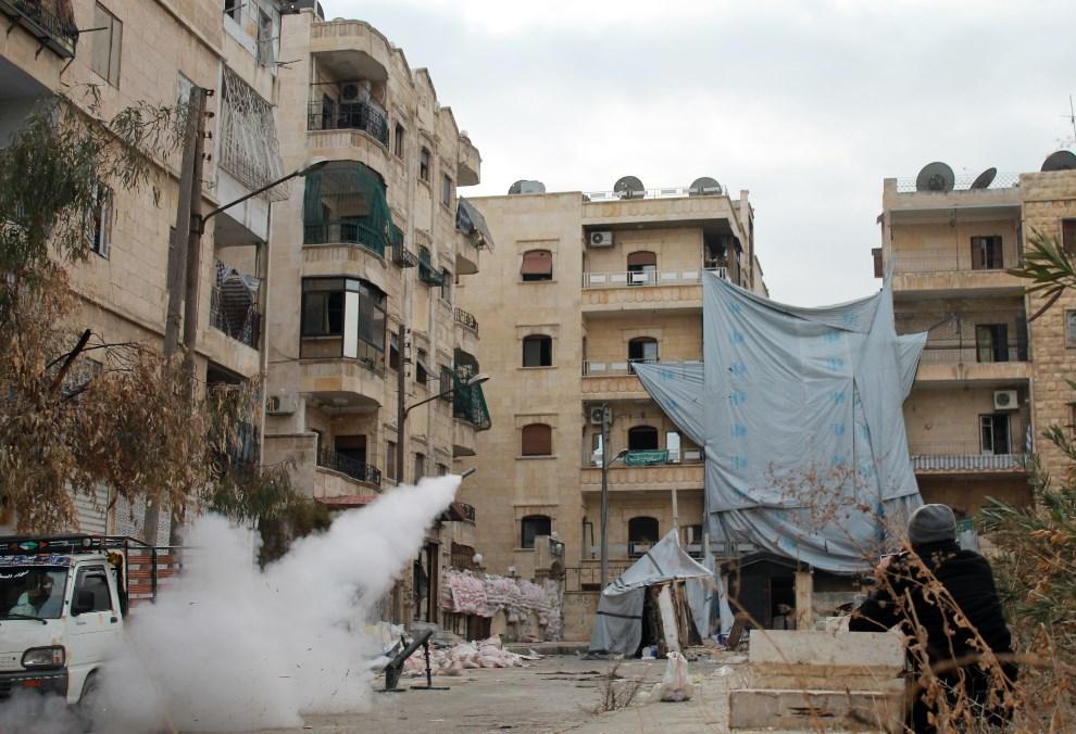 18.SYRIA, Aleppo, 12 stycznia 2014: Rebelianci odpalają rakietę domowej produkcji. AFP PHOTO / MAHMUD AL-HALABI