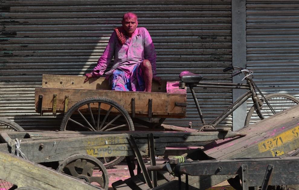 18.INDIE, New Delhi, 17 marca 2014: Rikszarz pokryty kolorowym proszkiem. AFP PHOTO /SAJJAD HUSSAIN