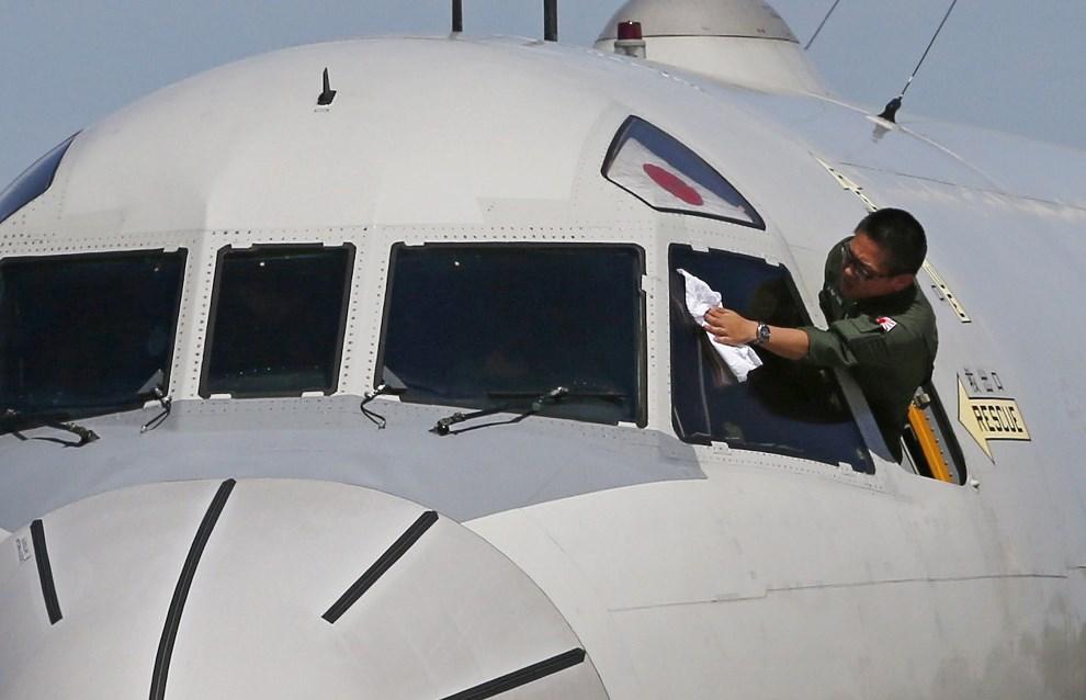 18.AUSTRALIA, Perth, 24 marca 2014: Członek załogi japońskiego samolotu ratowniczego Lockheed P-3C przed startem. AFP PHOTO / POOL / Jason Reed