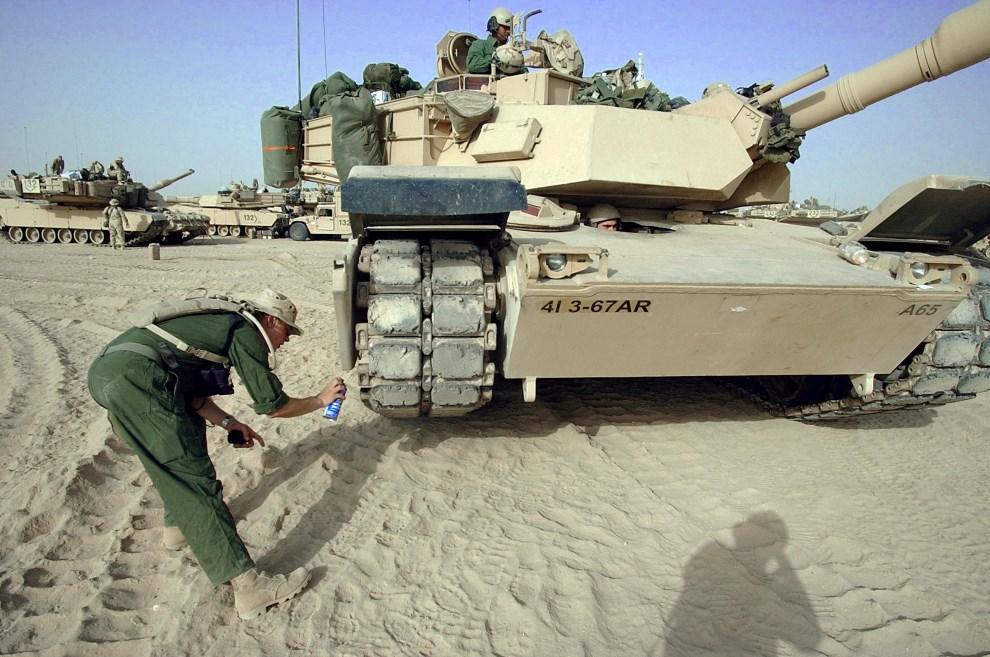 19.KUWEJT, 15 kwietnia 2003: Członek załogi smaruje łączenia gąsienic. AFP PHOTO/Roberto SCHMIDT