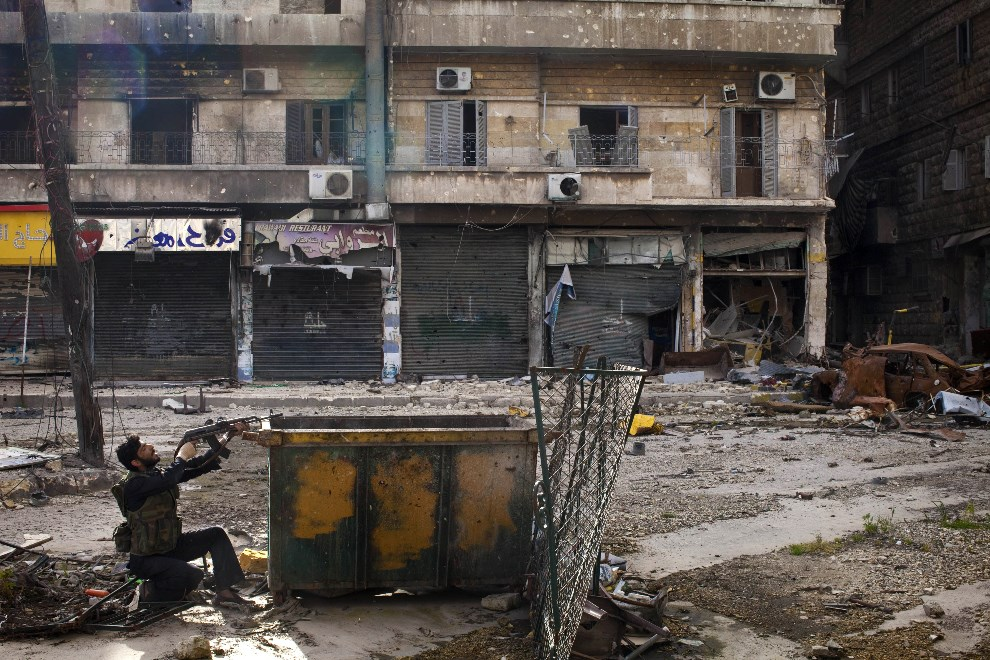 19.SYRIA, Aleppo, 16 marca 2013: Rebeliant ostrzeliwuje pozycje rządowe na ulicy w Aleppo. AFP PHOTO/JM LOPEZ