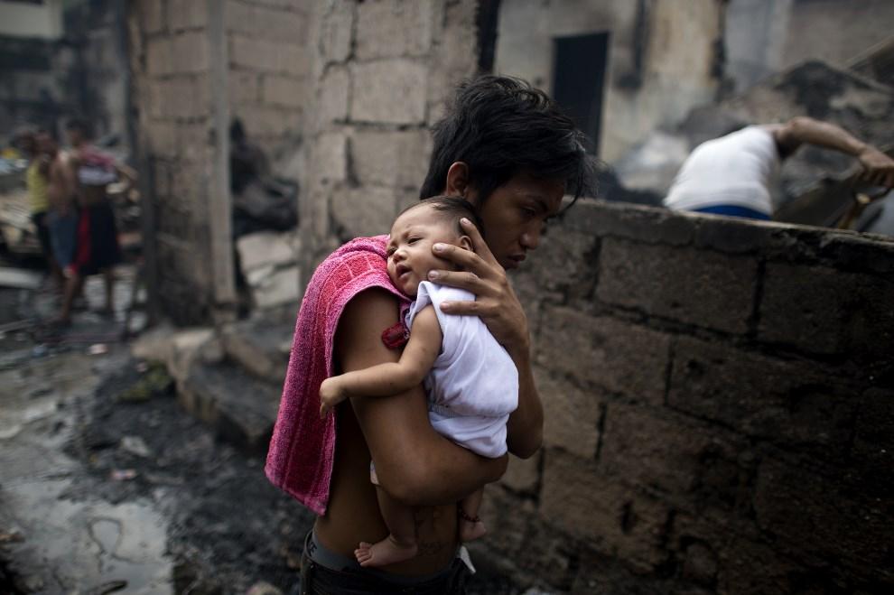 19.FILIPINY, Manila, 23 marca 2014: Mężczyzna z dzieckiem ewakuowani z płonących slumsów. AFP PHOTO / NOEL CELIS