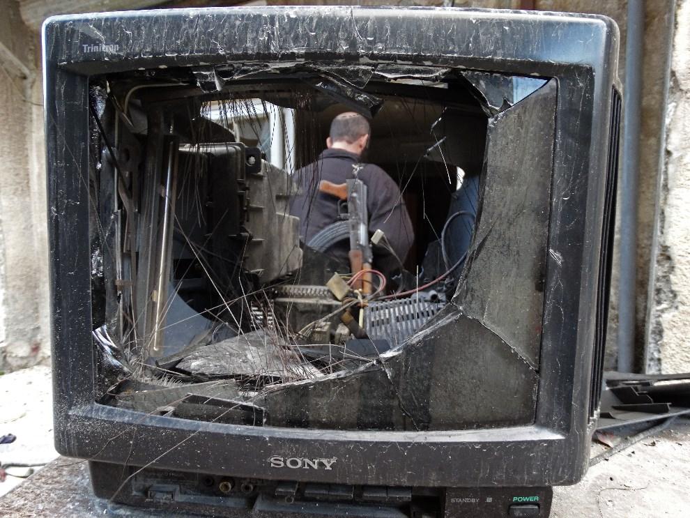 1.SYRIA, Aleppo, 18 września 2013: Rebeliant widziany przez rozbity telewizor. AFP PHOTO / MAHMUD AL-HALABI