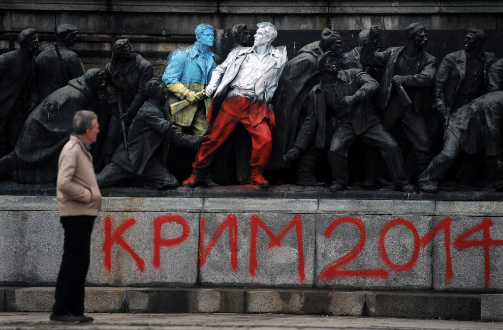 1.BUŁGARIA, Sofia, 5 marca 2014: Mężczyzna patrzy na pomnik Armii Czerwonej pomalowany w państwowych kolorach Ukrainy i Polski. AFP PHOTO / NIKOLAY DOYCHINOV
