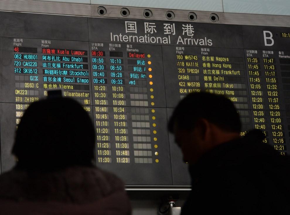 1.CHINY, Pekin, 8 marca 2014: Tablica przylotów z informacją o opóźnionym locie z Kuala Lumpur. AFP PHOTO/Mark RALSTON