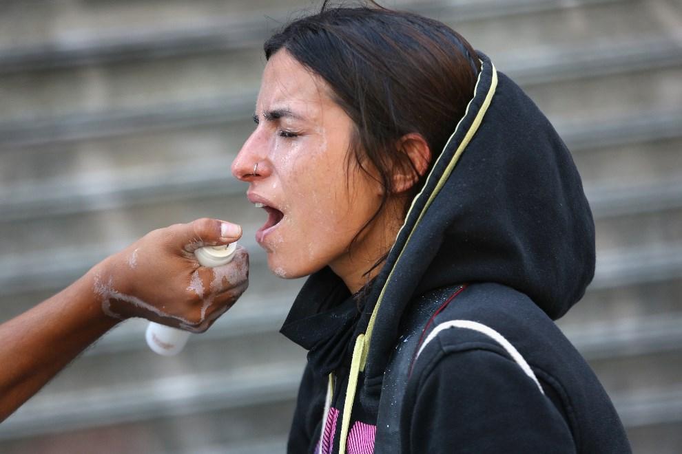20.WENEZUELA, Caracas, 2 marca 2014: Protestująca spryskiwana octem, aby zminimalizować skutki działania gazu łzawiącego. (Foto: John Moore/Getty Images)